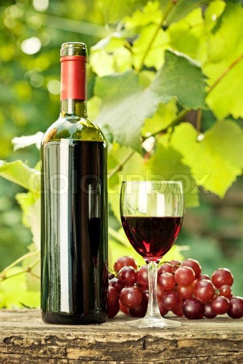 Red wine bottle, one glass and bunch of grapes on old